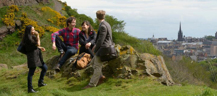 Undergraduate students on Arthur's Seat with panoramic view of the city in the background